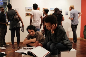 Viewers engaging with photographer, Jerry Gaegane's photo book and sound-scape recording.