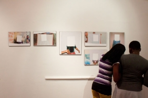 Viewers reading the supporting text of the body of work displayed.