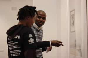2011/2012 Edward Ruiz recipient Jabulani Dhlamini, explaining his work to an audience member during his exhibition opening.
